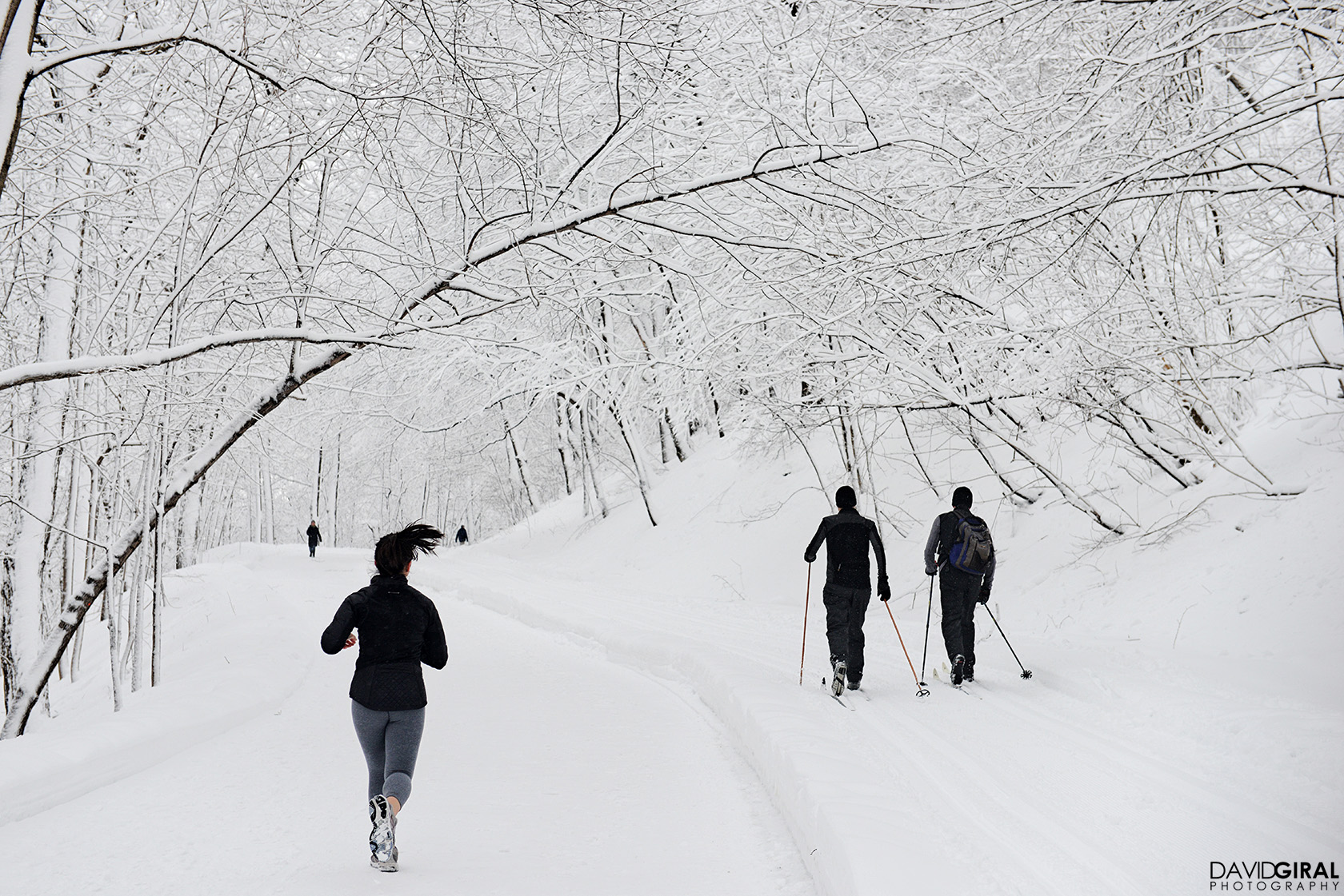 Woman running and men cross-country skiing at Mont Royal Park in Montreal