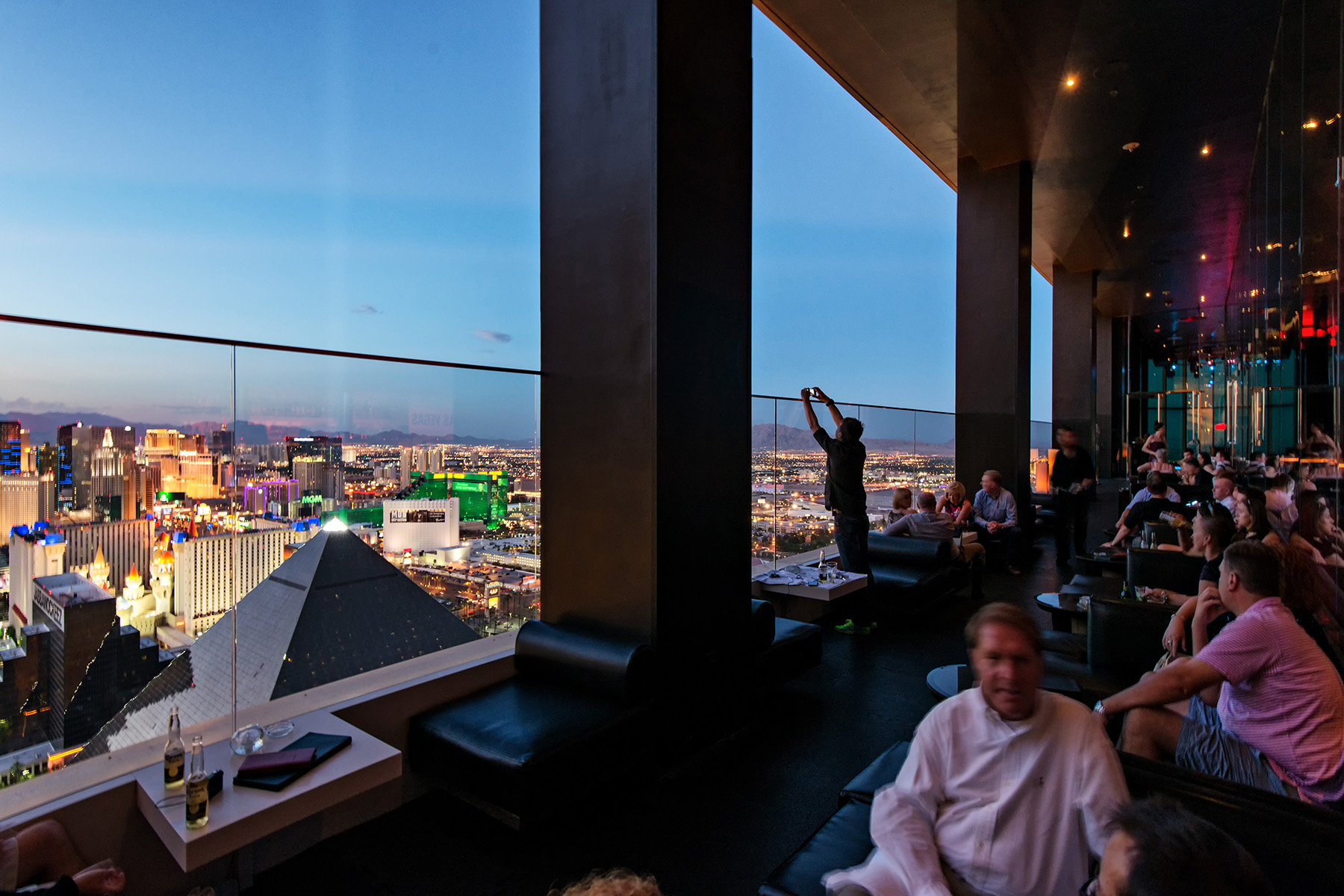 People enjoying drinks and cocktails at the THEHotel MiX Lounge terrace and Las Vegas Skyline at the blue Hour