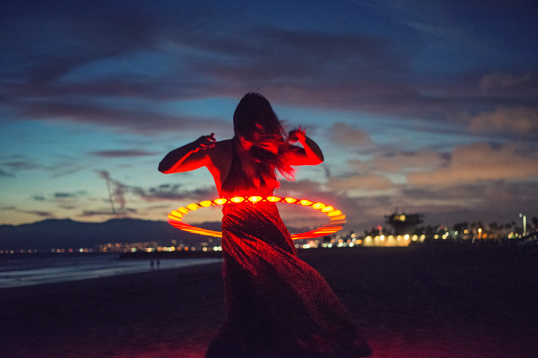 Woman playing with a hulla hoop on the beach at dusk